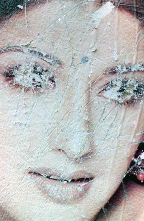 Defaced eyes on a poster. Brick Lane 2000
