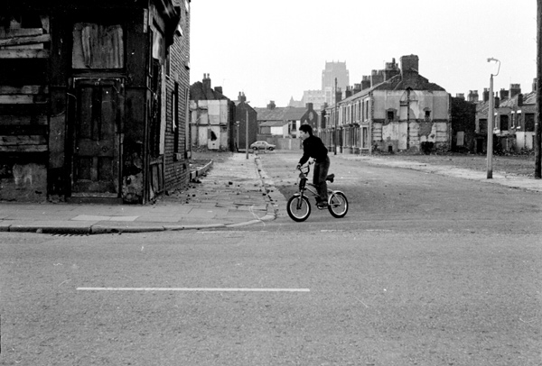 Boy riding a bicycle in Liverpool, 1979