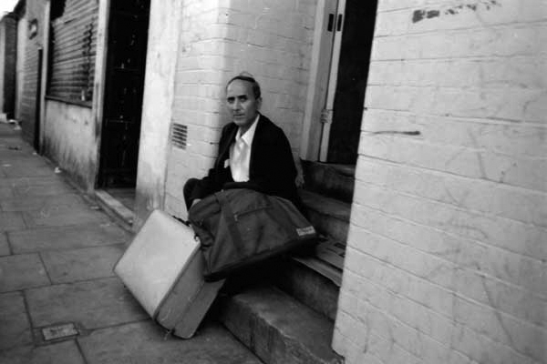 Man with suitcase rests on steps, Brick Lane c. 1983