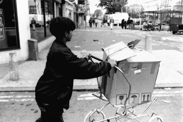 Boy pushing a cardboard box on a pram chassis, c.1985