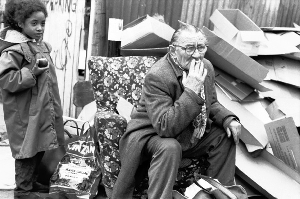 Man sitting on abandoned chair off Brick Lane 1984