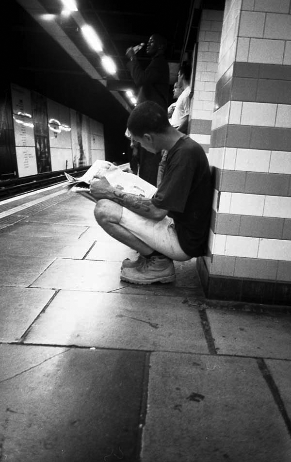 Reading a newspaper. Mile End underground, London c. 2000