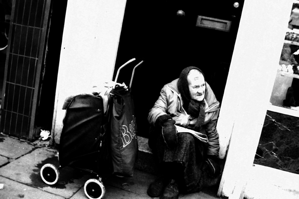 Bag lady in Spitalfields resting on a door step.