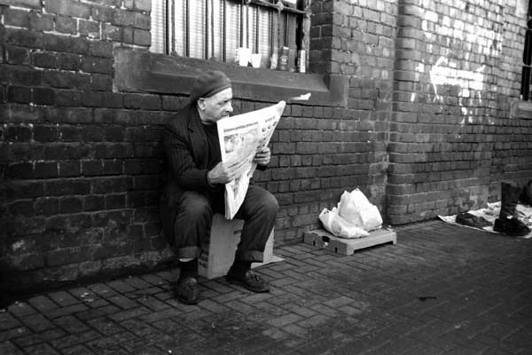 Man reading a newspaper. Bishopsgate Goods Yard c. 2000