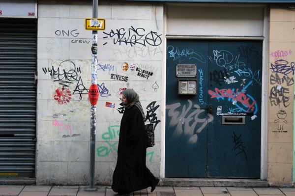 Woman walking past a wall covered in graffiti, Fashion Street 2008