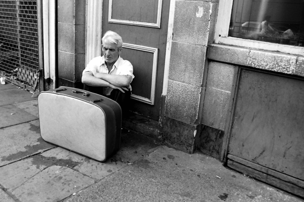 Man with a suitcase sleeping next to the Grave Maurice pub, 1983