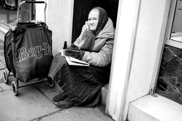 Bag lady in Spitalfields resting on a door step, 1987