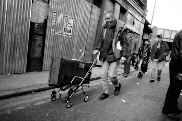 Man with a customised push chair pushing a suitcase, Brick Lane 1983