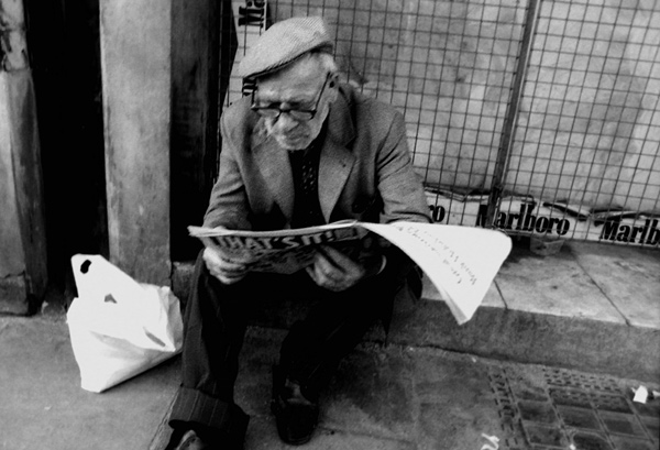 Man reading a paper on Whitechapel Road, 1984