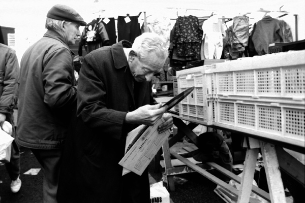 A man examining the condition of a LP. Sclater Street market, 1986
