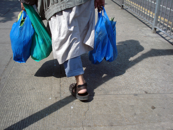 A man carrying plastic bags on old Montague Street