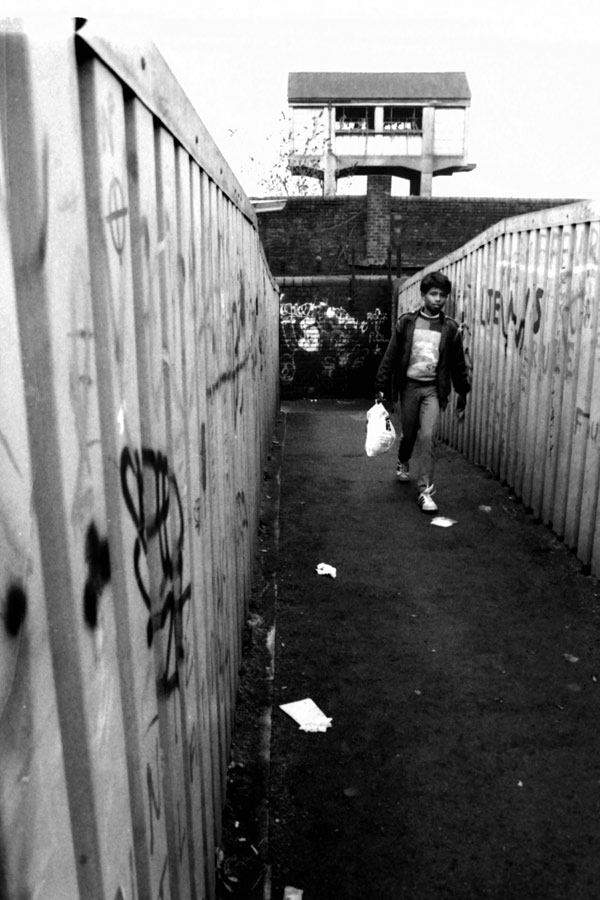 Boy walks over bridge, Spitalfields 1988