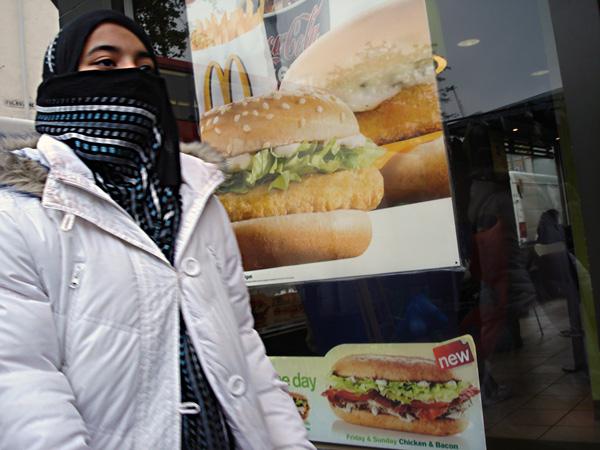 Young woman passes burger advertisement