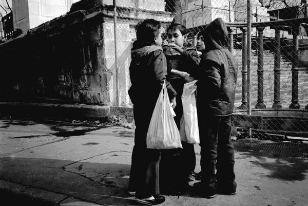 Four boys gather around a bollard outside Christ Church, Spitalfields