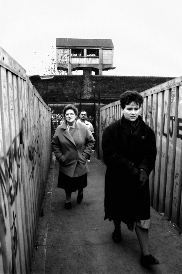 Three people cross a bridge, Spitalfields 1984