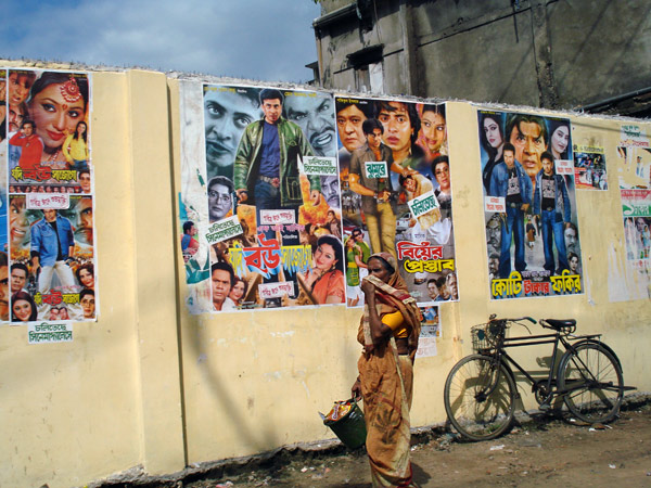 A woman walks past a wall plastered with cinema posters