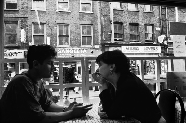 Young man & woman in conversation in the Clifton Cafe, Brick Lane 1989.