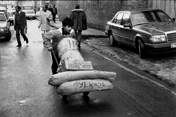 Boy pushing a trolley laden with goods, Brick Lane 1983