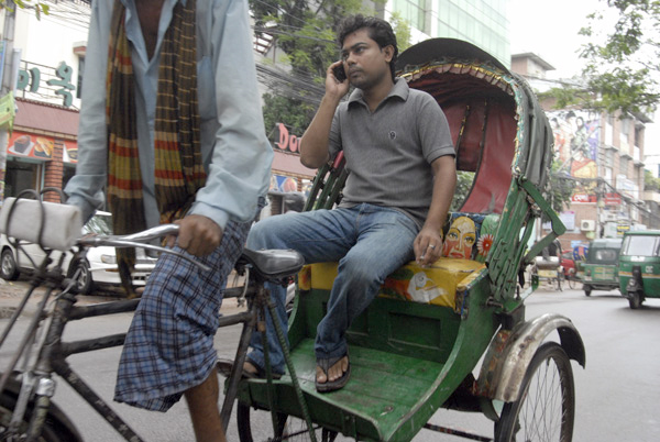Rickshaw driver with passenger using a mobile phone, Dhaka Bangladesh 2008