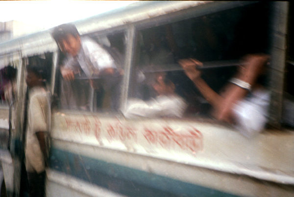 A passenger leans out of the window of a bus before it stops at a bus stop. Dhaka, Bangladesh1991
