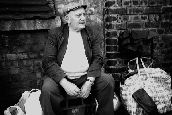 Man takes a rest against the wall of the former Bishopsgate Goods yard, 2001