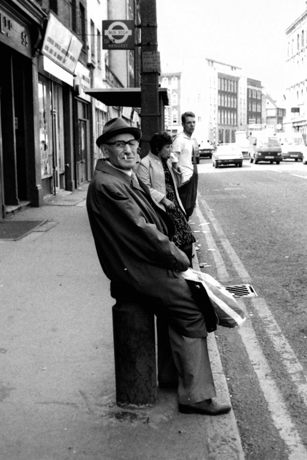 Man sitting on a bollard next to a bus stop, Commercial Street 1986
