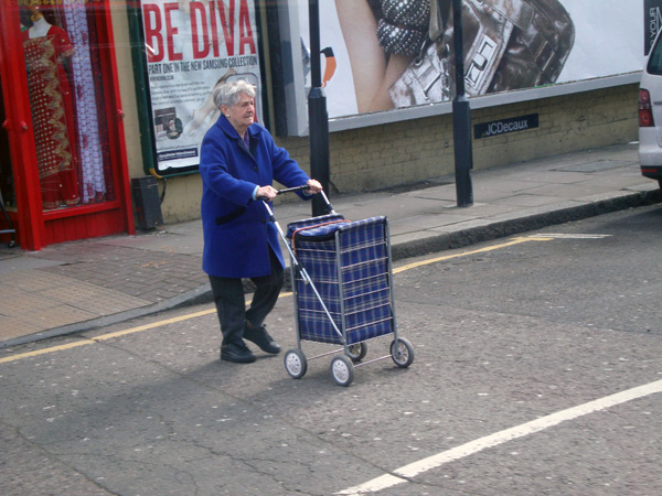 Lady pushes shopping trolley across Valance Rd. London 2006