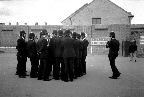 Police attending a BNP meeting in Stepney 1982. The fascists are in the school behind the photographer.