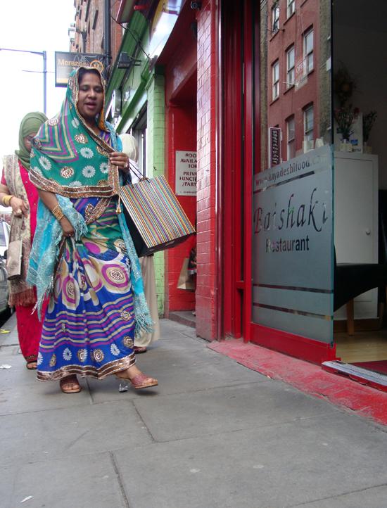 Woman in colourful dress. Brick Lane 2012