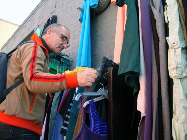 Man looking for clothes.Sclater Street, London