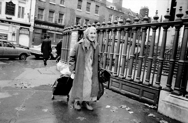 Woman with shopping trolley. Commercial Street, London 1985