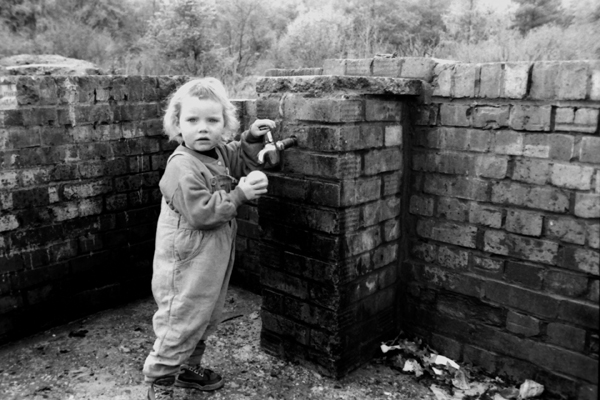 Child at the only source of running water on site. Essex, Late 1980