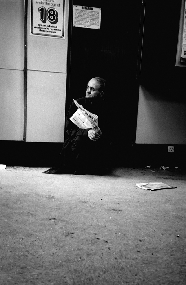 Man with newspaper. Betting shop, Whitechapel Road, London 1983