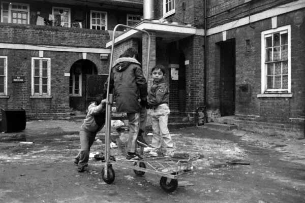 Children playing on a luggage carrier from a railway station. Early 1980's