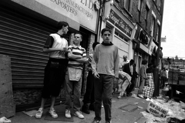 Young men take a break from their market stalls. Sclater Street, London 1985
