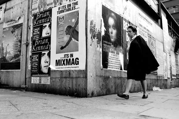 Pedectrian in Aldgate pass a building site. London 1987