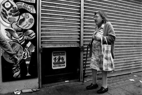 Woman walking on Bethnal Green Road, London c.1985