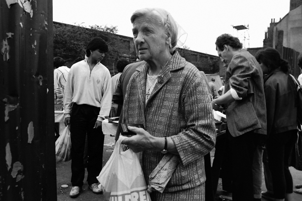 Woman with shopping bag, umbrella and cigarettes. Sclater Street, London c.1985
