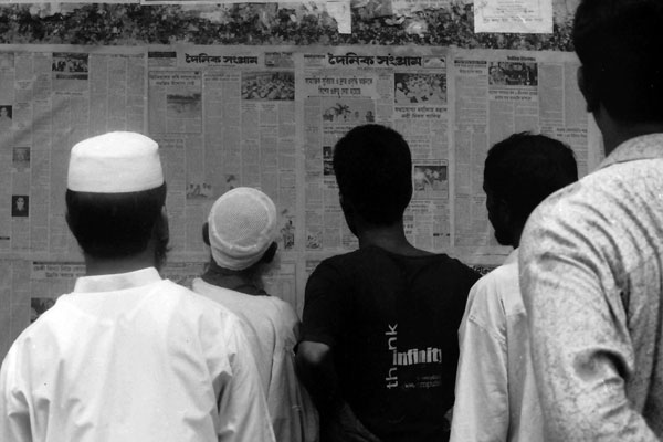 Reading a daily newspaper in Dhaka. Bangladesh 1991