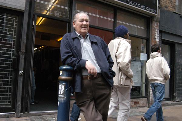 Man leaning on a bollard, Brick Lane 2010
