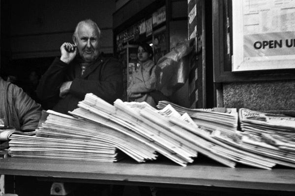 Man selling newspapers at Mile End Station, London c.2002