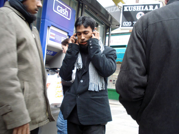 Man with two mobile phones, Whitechapel 2013