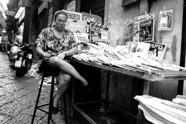 Woman selling newspapers on the street in Naples, Italy 1988