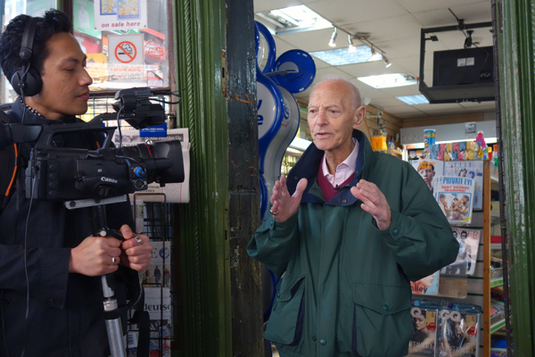 Harvey being filmed by Hazuan Hashim at the entrance to a Soho newsagents.