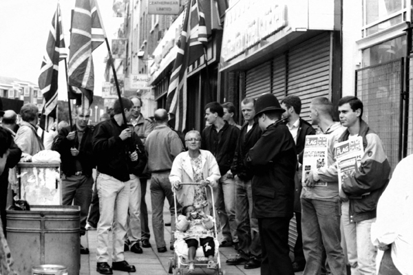 Woman wheels her pushchair through a crowd of BNP supporters at the the intersection of Brick Lane with Bethnal Green Road 1992