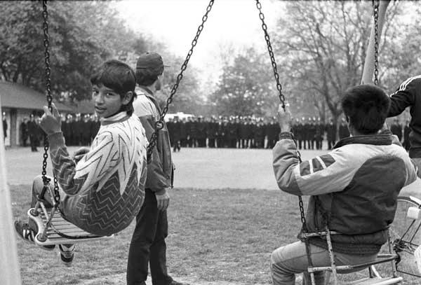 Children play on swings in Plashet park, Newham 1985