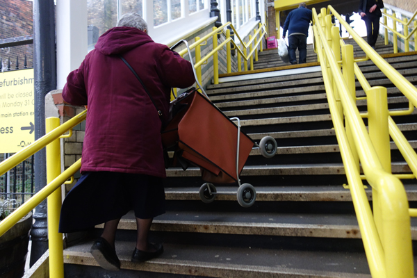 A pensioner struggles up the stairs of a Merseyrail station. Pensioners and the disabled often depend on the guard on the train.