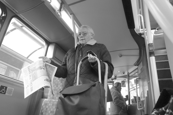 Woman with newspaper.On the bus. Liverpool, 2017.