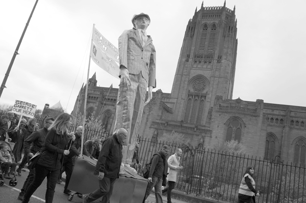 Statue of working class hero George Garrett passes the Anglican Cathedral. Liverpool May 2017.