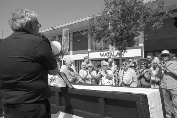 A speaker addresses the crowd in front of a coffin that signifies the death of the C4 & C5 bus routes.